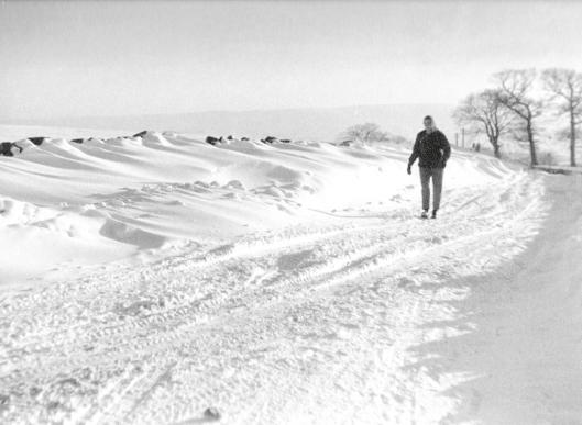 woman walking across snowy landscape