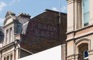 """Old shop sign on side of building """"Frank East's"""""""