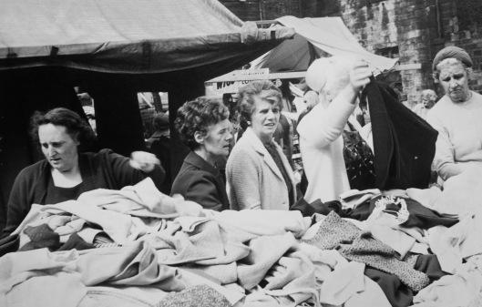 Women rummaging through clothing stalls at an open air market
