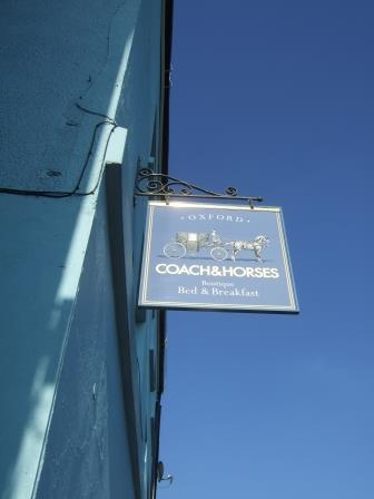 Blue sign against a blue building and a blue sky